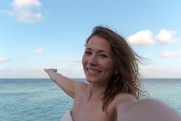 young woman in honeymoon taking a selfie. Sea as Background