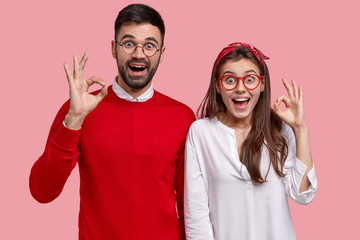 Charismatic positive Caucasian girlfriend and boyfriend make okay gesture, say dont worry, assert everything is under control, pose self assured, smile broadly, isolated over pink background