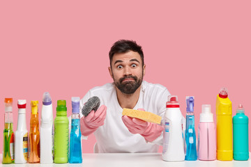 Photo of bearded atrractive busy husband holds two sponges, raises eyebrows with surprisement, wears rubber protective gloves, sits at desk cleaning supplies for tidying up room, brings house in order