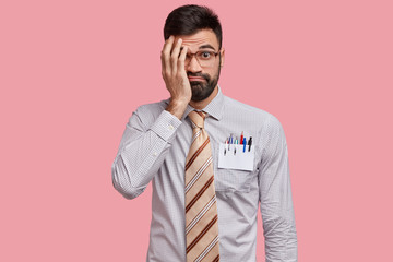 Displeased unshaven young man has shy expression, covers face with hand, wears big optical glasses, formal shirt, has surprised gaze, isolated over pink background. Oh no, dont bother me, please