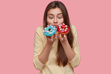 Horizontal shot of shocked pretty European woman holds blue and red doughnuts, smells aromatic confectionery, wears yellow clothes, models over pink background. Junk food and dessert concept