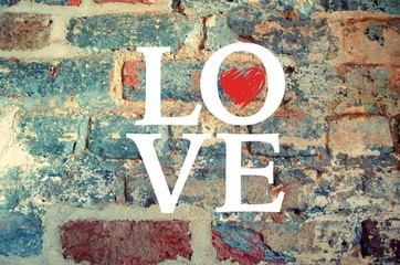 The word Love written out over a brick wall background