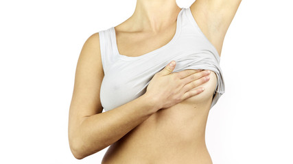 Woman white shirt examining her breast for lumps or signs of breast cancer