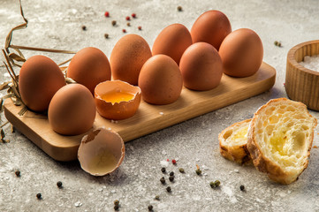 Close up. Traditional ingredients for breakfast. Fresh farm eggs in a wooden tray, next to chunks of baguette with cheese and spices. Copy space.