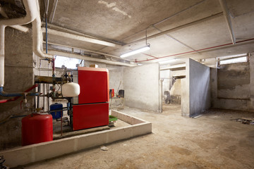 Basement with red heating boiler and dirty floor in old house interior