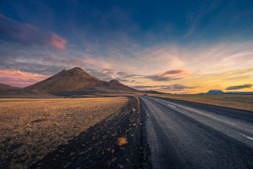 Iceland. Colorful landscape at sunset with dark road
