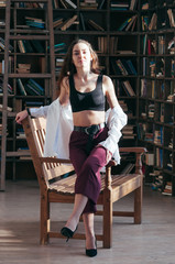 Attractive young female wearing black sport bra lingerie and white shirt unbuttoned, casual fashion style, sitting on wooden chair, bookshelves in the backdrop. Long hair, sensual beautiful seductive