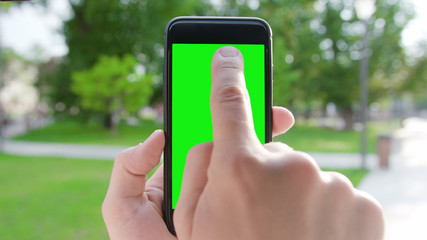 Lublin, Poland - July 2018: A hand holding a phone with a green screen in a public park. Close-up shot. Soft focus