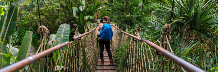 Woman with a backpack taking photographs on a suspension bridge in the jungle panorama
