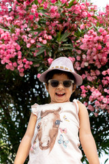 Beautiful girl with glasses and hat in front of flowers