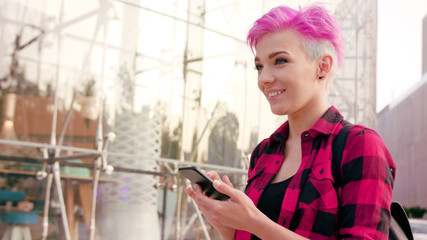 A young woman with a pink short hair using a phone in the city street. Close-up shot. Soft focus. Dolly shot.