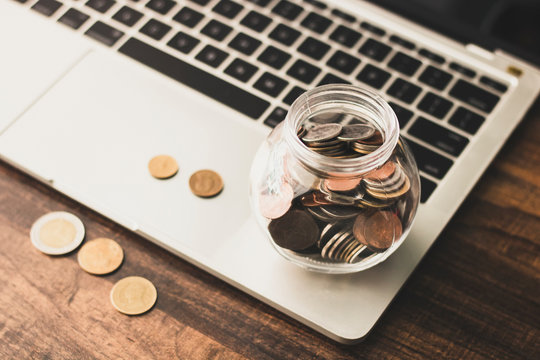 save and finance concept, money coin in jar with laptop on table