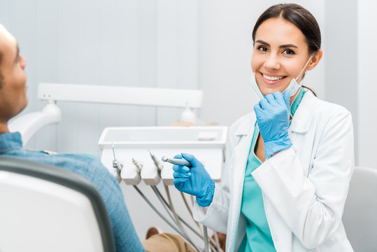cheerful female dentist holding drill and smiling near patient