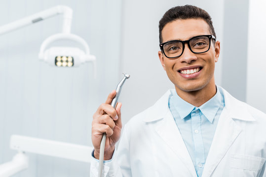 smiling african american dentist in glasses holding drill