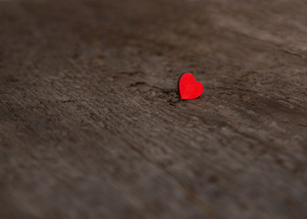 Single small wooden red heart on an old dry wooden board for Valentine's Day close up