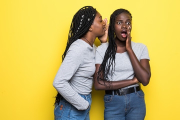 Portrait of two happy young african women sharing secrets isolated over yellow background