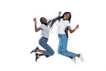 Two cheerful african girls jumping over white background
