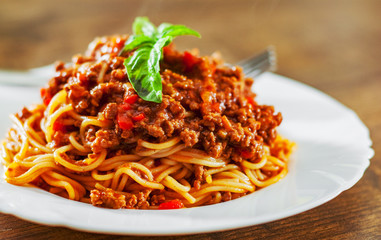 Traditional pasta spaghetti bolognese in white plate on wooden table background