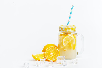 A jar of homemade lemonade and lemons on a white background.