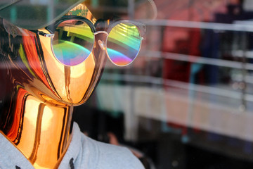 A reflective metallic gold mannequin wearing round sunglasses in a shop window