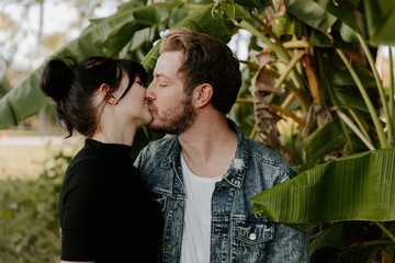Portrait of Two Cute Modern Caucasian Beautiful Young Adult Guy Boyfriend Lady Girlfriend Couple Hugging and Kissing in Love in Nature with Green Plants Trees in the Outdoor Park