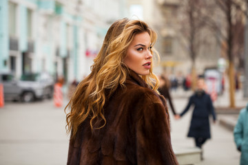Happy Beautiful young blonde woman in mink fur coat