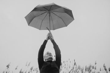 A man holds an umbrella above his head, on outstretched hands. Financial safety. Raining day in city park view, risk and crisis concept.