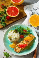 Grilled Salmon with Grapefruit and Orange Sauce and rice garnish on a light stone or concrete table.