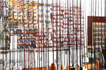 Stand with different fishing rods in sports shop