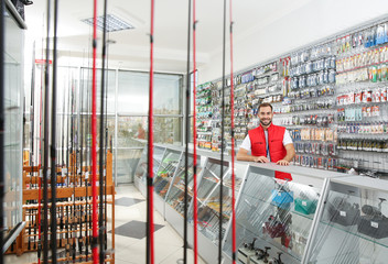 Salesman standing near showcase with fishing equipment in sports shop
