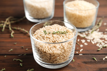 Glass with raw unpolished rice on wooden table