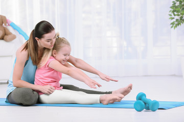 Woman doing fitness exercises with daughter at home
