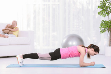 Woman doing fitness exercises while her daughter sitting on sofa at home