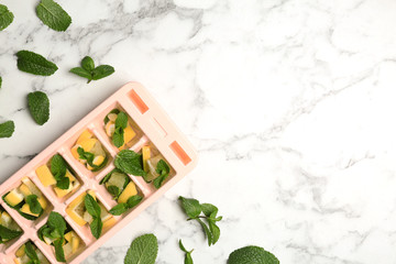 Ice cube tray with mint and lemon on marble background, top view. Space for text