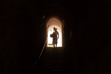 Tourist woman at the entrance of medieval dark stone tunnel, Ponza Island, Italy. Fashion dress, hat, basket.