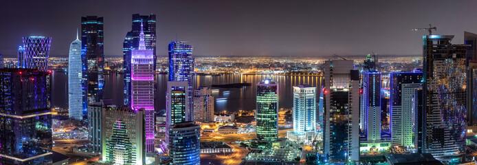 Panorama des Zentrums von Doha in Katar mit den bunt beleuchteten, modernen Wolkenkratzern Fototapete