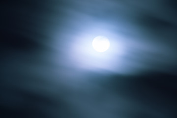 Full moon shining behind fast moving clouds; movement blur