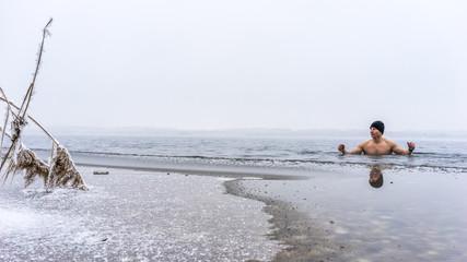 Junger Mann mit Mütze beim Eisbaden
