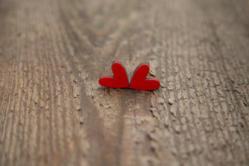 Two wooden red hearts on an old dry wooden board for Valentine's Day close-up.