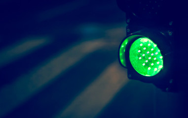 Green traffic light with pedestrian in background in rainy night Fotomurales