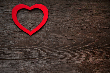 The red heart is located on an old wooden brown dry board. Valentine's Day card