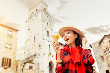Young hipster traveler eating ice-cream in old Italian town