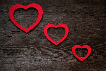 Three red hearts are located diagonally on an old wooden brown wooden board, one smaller than the other. Valentine's Day Card
