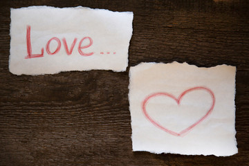 The word love is written in red pencil on a piece of paper, the heart is drawn in red pencil on a piece of paper. everything is located on an old wooden board