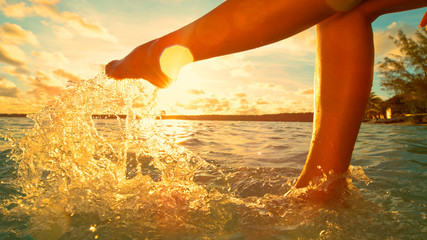 LENS FLARE: Unrecognizable woman having fun kicking the refreshing ocean water.