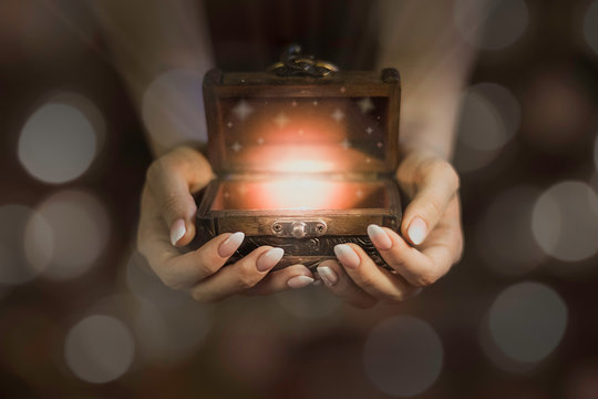 opened wooden magic box on hands, lights from little chest, dreams in hands, believe in miracle