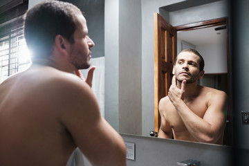 Shirtless Attractive Man Looks at Himself in Front of Mirror