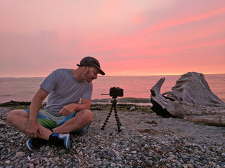 Caucasian Man Smiling While Taking a Photo of Sunset on Beach