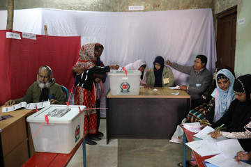 A woman puts her ballot paper into the ballot box during the general election in Dhaka