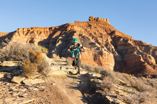 A woman rides a mountain bike over a small drop on the Jem trail below Gooseberry mesa in Southern Utah.
